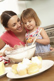 Young Girl Helping Mother To Bake Cakes In Kitchen Stock Images
