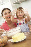 Young Girl Helping Mother To Bake Cakes In Kitchen Stock Photo