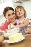 Young Girl Helping Mother To Bake Cakes In Kitchen Royalty Free Stock Photos
