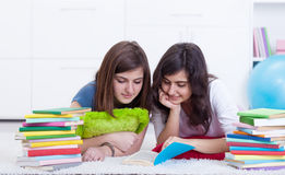 Young girl helps her friend learning Royalty Free Stock Images