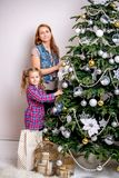 A young girl helps her mother to decorate the family Christmas tree stock photos