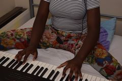 Young girl on her bed playing a keyboard Stock Photos
