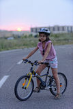 Young girl and her bicycle in road Royalty Free Stock Photo