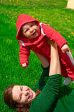 Young girl and her child lie on the green grass. Young mother and her child lie on the green grass. They are laughing. Green background. Red clothes on the baby Royalty Free Stock Image