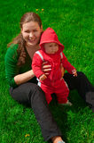 Young girl and her child sit on the green grass. Young mother and her child sit on the green grass. They are smiling. Green background. Red clothes on the baby Stock Images