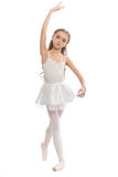Young girl in her dance clothes reaching down to touch her foot. Royalty Free Stock Image