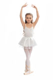 Young girl in her dance clothes reaching down to touch her foot. royalty free stock photography