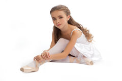 Young girl in her dance clothes reaching down to touch her foot. Royalty Free Stock Photos