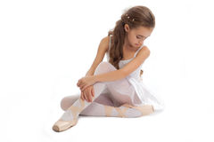 Young girl in her dance clothes reaching down to touch her foot. Stock Photo
