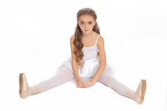Young girl in her dance clothes reaching down to touch her foot. Stock Photos