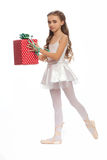 Young girl in her dance clothes reaching down to touch her foot with gifts in hand Stock Photos
