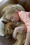 Young girl and her dog cuddling at home Stock Photos