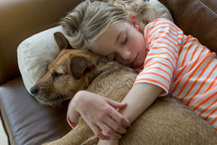 Young girl and her dog cuddling at home Stock Photography