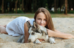 Young girl and her dog (husky) walking in autumn in a city park Royalty Free Stock Photos