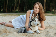 Young girl and her dog (husky) walking in autumn in a city park Royalty Free Stock Photo