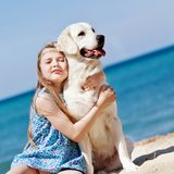 Young girl with her dog by seaside. Playing on the sand Royalty Free Stock Image