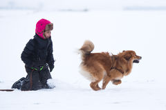 Young girl with her dog in the snow Royalty Free Stock Images