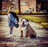 Young girl and her dog. Young 1 years old english bulldog and little girl 1-2 years old on a walk Stock Image