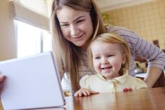 Young girl with her elder sister looking at tablet royalty free stock photography