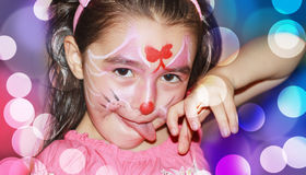 A YOUNG GIRL WITH HER FACE PAINTED. A happy young girl with face-paint on after a carnival royalty free stock photo