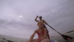 Young girl with her father ride on Paddle Board. Mainly cloudy. View from the board. stock video
