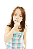 Young girl with her finger over her mouth Royalty Free Stock Photo