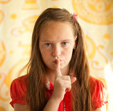Young girl with her finger over her mouth Royalty Free Stock Images