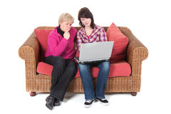 Young girl with her grandma. Young girl is showing her grandma something interesting at her laptop Stock Image