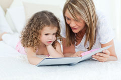 Young girl and her grandmother. Young girl reading a book with her grandmother Stock Photo