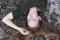 Young girl with her hair lying on a stone background. Royalty Free Stock Photos