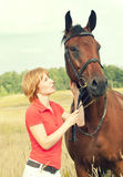 Young girl  with her horse in field Stock Photography