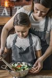 Girl and mother making salad royalty free stock photography