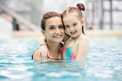 Young girl and her mother hugging in the pool. royalty free stock photos