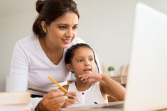 Young girl and her mother. Looking at the screen of the laptop and drawing stock image