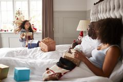Young girl in her parents� bedroom carrying presents on Christmas morning, parents sitting up in bed, side view royalty free stock images