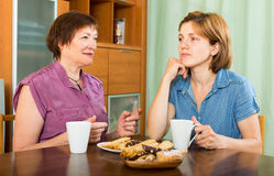 Young girl and her pensioner mother drinking coffee Royalty Free Stock Photography