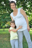 Young girl and her pregnant mother in the city park Stock Images