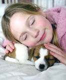 Young girl and her puppy sleeping on a bed Royalty Free Stock Photography