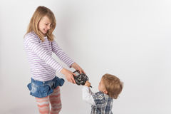 Young girl and her small brother fighting for the drone remote c Royalty Free Stock Photography