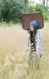 A young girl with her suitcase. Traveling means hard work sometimes Royalty Free Stock Images