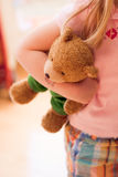 Young girl and her teddy bear. A young girl clutches her stuffed teddy bear stuffed animal Royalty Free Stock Photos