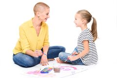 Young girl and her therapist in child occupational therapy session painting with watercolors. Child therapy concept.