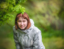 Young girl hides from the rain under a bush Royalty Free Stock Image