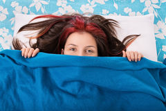 Young girl hiding behind a blanket on her bed Royalty Free Stock Photography