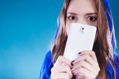 Young girl hiding behind phone. Royalty Free Stock Images