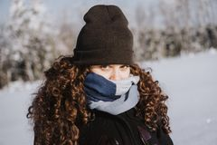 Young girl hiding from the winter cold. Young girl hiding from the cold behind heavy clothes and a scarf Royalty Free Stock Photos
