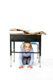 Young girl hiding under a school desk Royalty Free Stock Image