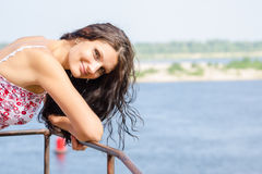 Young girl in high spirits leaned on old metal railings on the background of the river Stock Photography