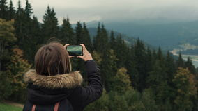 Young girl hiker is shooting video of beautiful misty mountain landscape on mobile phone camera. Lifestyle adventure. Back view, toning, 4k stock video