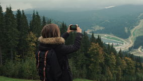 Young girl hiker is shooting video of beautiful misty mountain landscape on mobile phone camera. Lifestyle adventure. Back view, toning, 4k stock footage